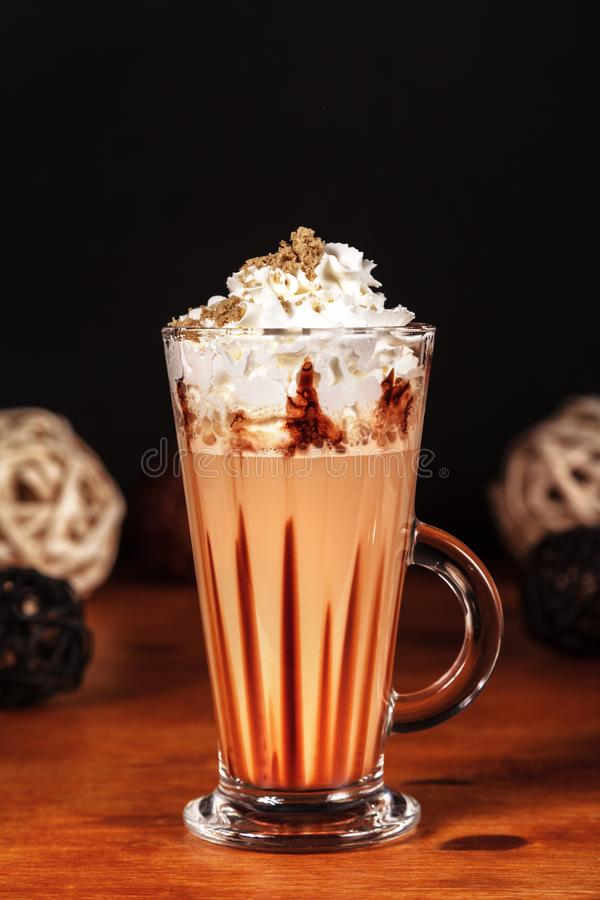 Υπέροχα σχεδιασμένος latte καφές macchiato με την κτυπημένη κρέμα και ψεκασμένος με το συντριμμένο halva, σε ένα σκοτεινό υπόβαθρ στοκ εικόνα με δικαίωμα ελεύθερης χρήσης