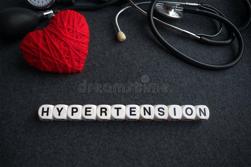 Υπέρταση καρδιών λέξης από τους άσπρους κύβους με τις επιστολές στο σκοτεινό BA στοκ εικόνα