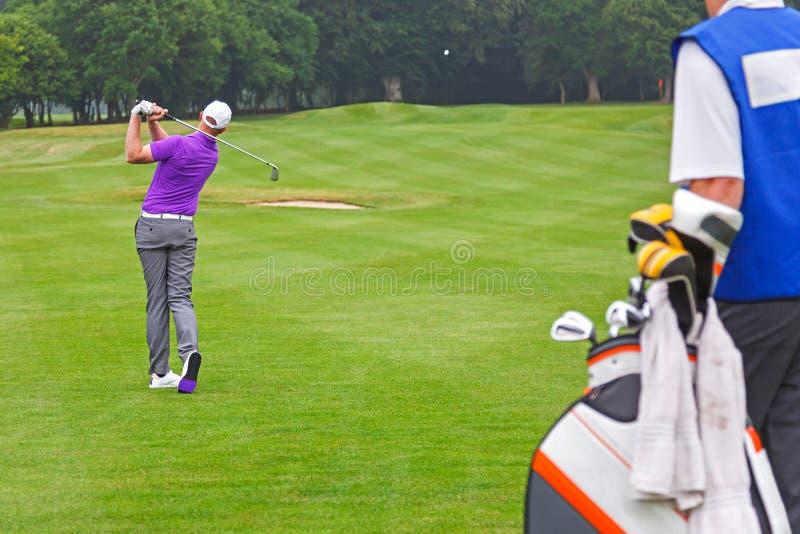 Υπέρ παίκτης γκολφ που παίζει έναν πυροβολισμό με caddy στοκ εικόνες