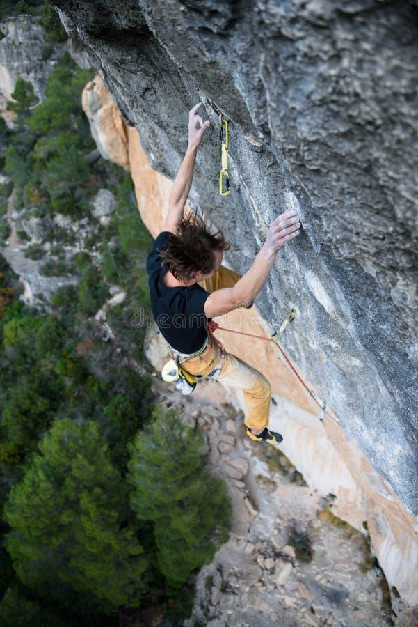 Υπαίθρια αθλητική δραστηριότητα Ορειβάτης βράχου που ανέρχεται ένα προκλητικό CLI στοκ εικόνα