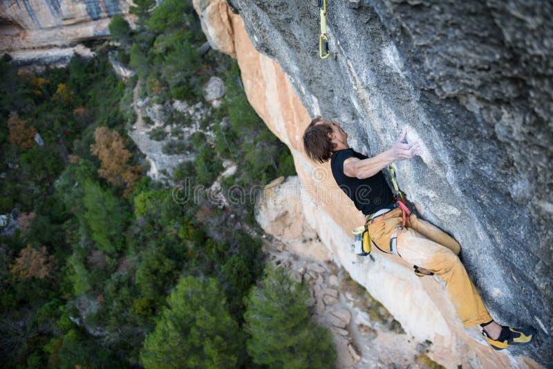 Υπαίθρια αθλητική δραστηριότητα Ορειβάτης βράχου που ανέρχεται ένα προκλητικό CLI στοκ φωτογραφίες