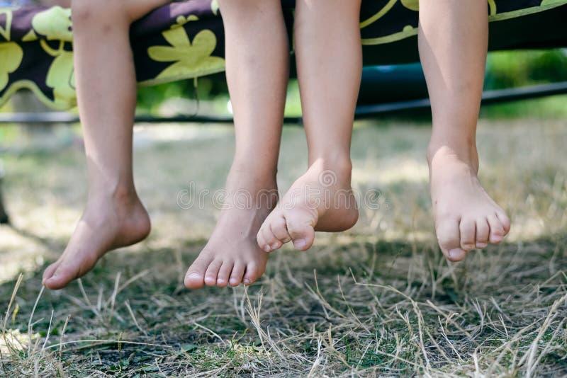 Υπαίθρια εικόνα δύο ποδιών παιδιών χωρίς παπούτσια Κινηματογράφηση σε πρώτο πλάνο των ευτυχών παιδιών που κάθονται στην ηλιόλουστ στοκ φωτογραφία με δικαίωμα ελεύθερης χρήσης