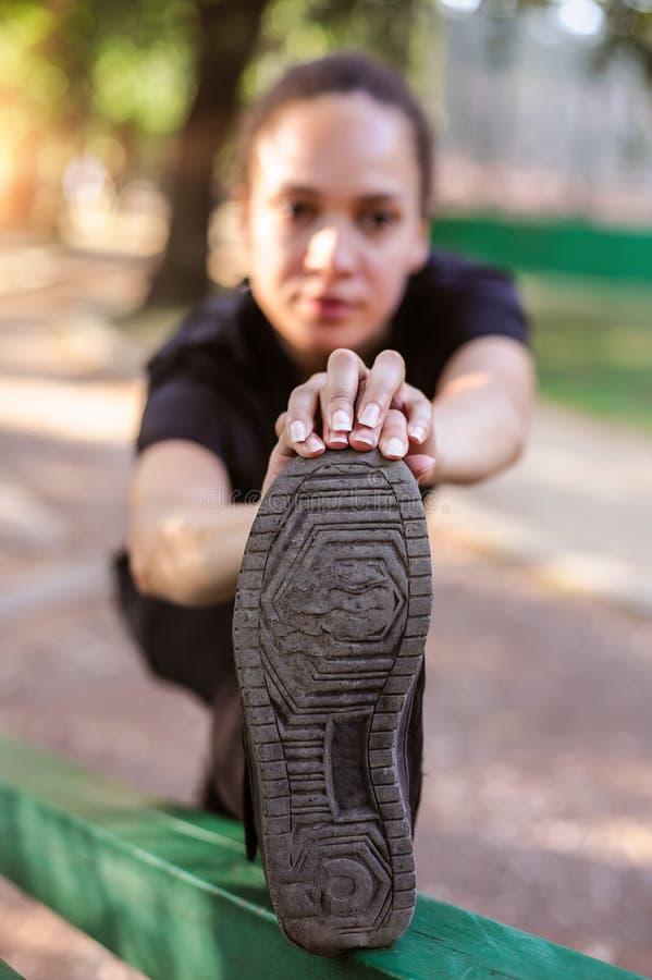 υπαίθρια εκπαιδευτικός Κατάλληλη νέα γυναίκα που τεντώνει τα πόδια της στοκ εικόνα