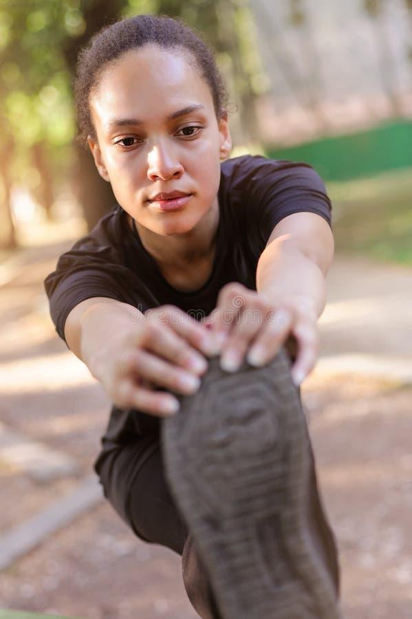υπαίθρια εκπαιδευτικός Κατάλληλη νέα γυναίκα που τεντώνει τα πόδια της στοκ φωτογραφίες με δικαίωμα ελεύθερης χρήσης