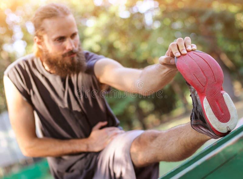 υπαίθρια εκπαιδευτικός Νεαρός άνδρας που τεντώνει τα πόδια του στοκ εικόνες με δικαίωμα ελεύθερης χρήσης