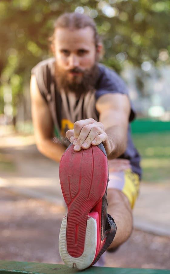 υπαίθρια εκπαιδευτικός Νεαρός άνδρας που τεντώνει τα πόδια του στοκ φωτογραφίες με δικαίωμα ελεύθερης χρήσης