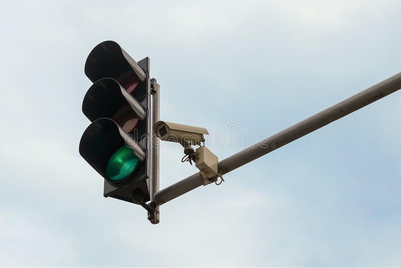 Υπαίθρια κάμερα παρακολούθησης και πράσινος φωτεινός σηματοδότης και οι δύο που εγκαθίστανται σε έναν πόλο επάνω από ένα οδόστρωμ στοκ φωτογραφία με δικαίωμα ελεύθερης χρήσης