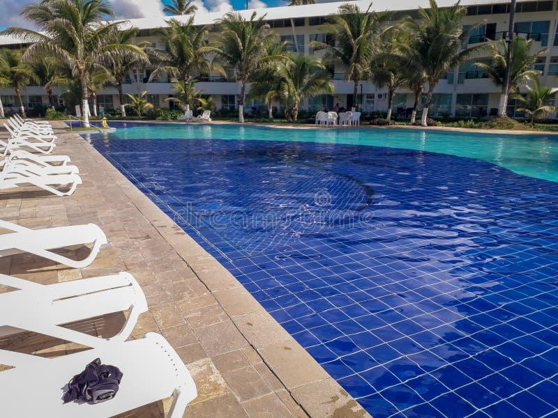 Υπαίθρια λίμνη στο ξενοδοχείο και θέρετρο με το φοίνικα και τις καρέκλες γύρω Βραζιλία 2019 στοκ εικόνα