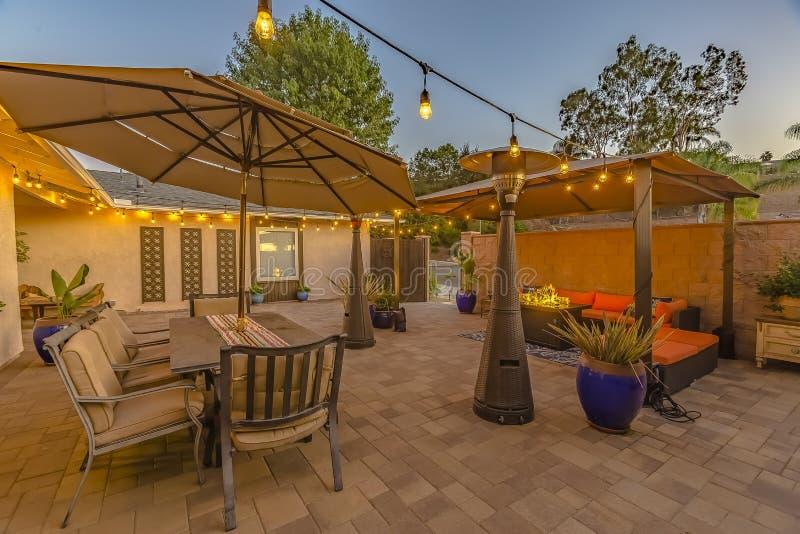 Υπαίθρια να δειπνήσει και να καθίσει περιοχή στο άνετο patio πετρών ενός σπιτιού στοκ εικόνα