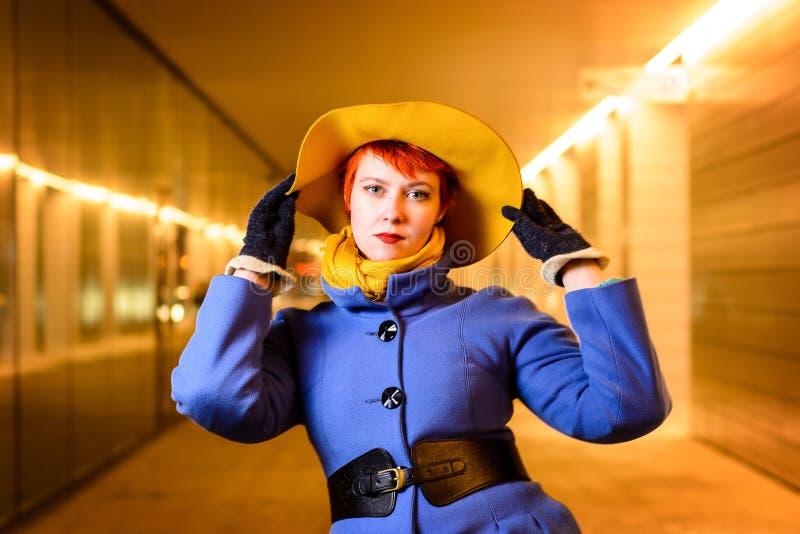Υπαίθρια πορτρέτο τρόπου ζωής του όμορφου redhead κοριτσιού σε μια στοά με τα φω'τα, αργά το βράδυ στοκ φωτογραφίες