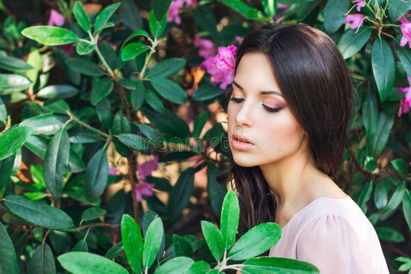 Υπαίθρια φωτογραφία μόδας της όμορφης νέας γυναίκας που περιβάλλεται από τα λουλούδια dof ανθών αζαλεών στενή ρηχή άνοιξη λουλουδ στοκ φωτογραφίες
