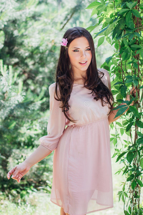 Υπαίθρια φωτογραφία μόδας της όμορφης νέας ευτυχούς χαμογελώντας γυναίκας που περιβάλλεται από τα λουλούδια dof ανθών αζαλεών στε στοκ φωτογραφία με δικαίωμα ελεύθερης χρήσης