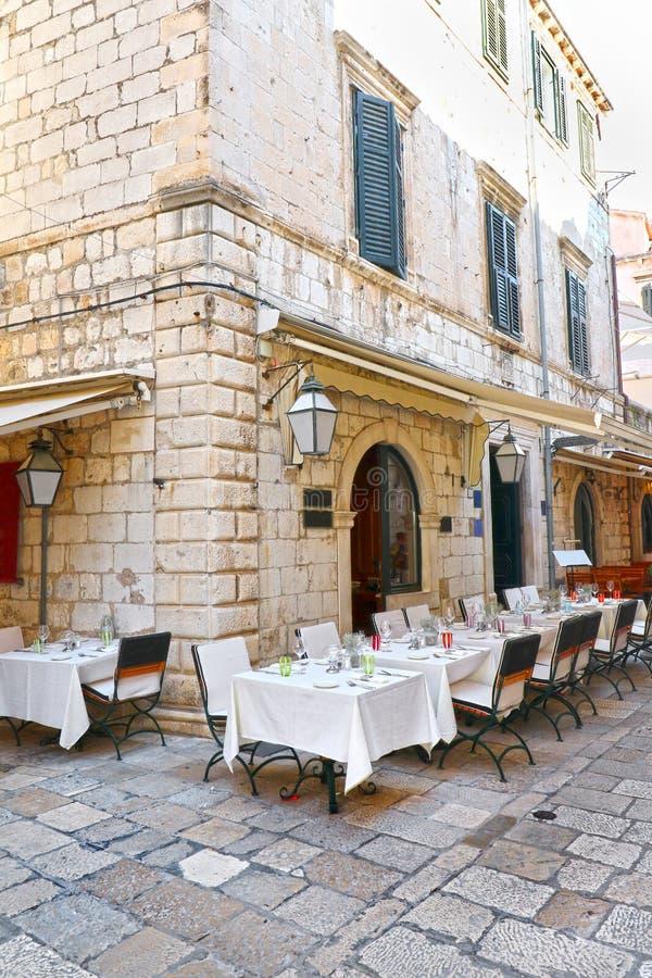 Υπαίθριες διατάξεις θέσεων εστιατορίων σε Dubrovnik, Κροατία Παλαιά πόλη Άσπρο να δειπνήσει λινού στοκ εικόνες