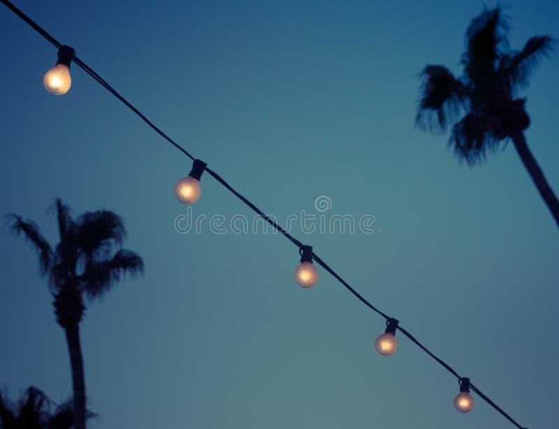 Υπαίθριες λάμπες φωτός γιρλαντών σειράς το βράδυ στοκ φωτογραφίες
