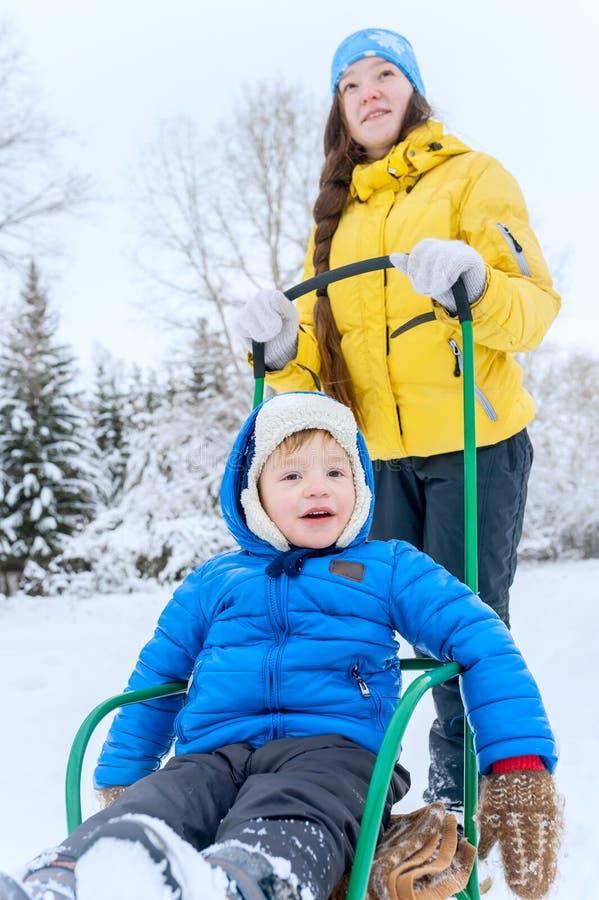 Υπαίθριοι περίπατοι Mom πορτρέτου με το γιο το χειμώνα Αυτή carr στοκ εικόνα με δικαίωμα ελεύθερης χρήσης