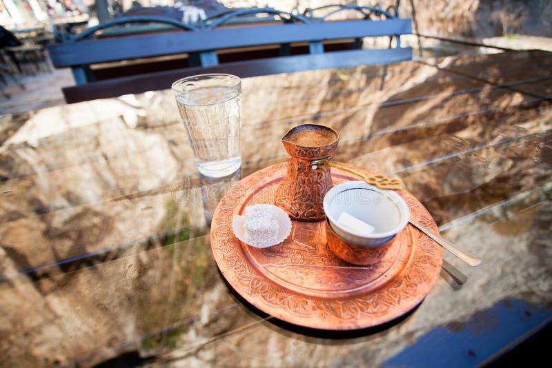 Υπαίθριος καφές με τον τουρκικό καφέ στο χαλκό cezve και ένα κομμάτι της τουρκικής απόλαυσης στον πίνακα γυαλιού στοκ εικόνα
