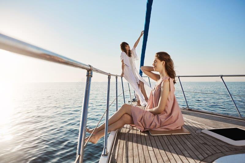 Υπαίθριος πυροβολισμός του τρυφερού και ελκυστικού ενήλικου θηλυκού, χρόνος εξόδων στη βάρκα Στάσεις κοριτσιών στο τόξο του γιοτ  στοκ φωτογραφία με δικαίωμα ελεύθερης χρήσης