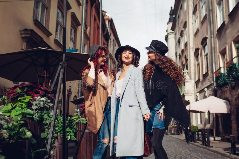 Υπαίθριος πυροβολισμός τριών νέων γυναικών που περπατούν στην οδό πόλεων Κορίτσια που μιλούν και που αγκαλιάζουν στοκ φωτογραφία