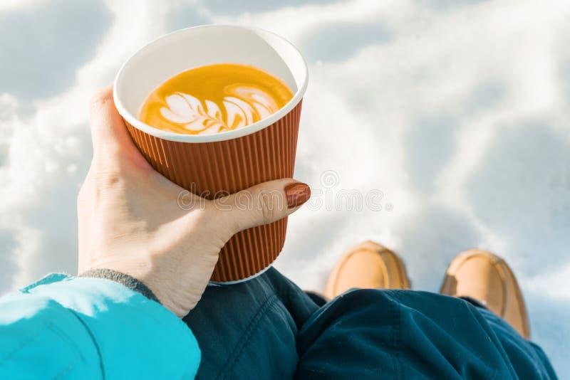 Υπαίθριος χειμώνας, χέρια της γυναίκας με το φλιτζάνι του καφέ, υπόβαθρο του χιονιού στοκ φωτογραφίες