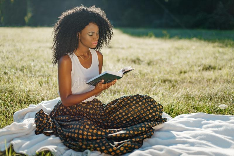 Υπαίθριο ηλιόλουστο πικ-νίκ Το λατρευτό νέο αφρικανικό κορίτσι με τις πράσινες σκιές ματιών στηρίζεται διαβάζοντας το βιβλίο στοκ εικόνα