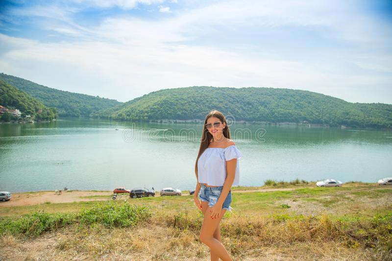 Υπαίθριο θερινό πορτρέτο της νέας αρκετά μακρυμάλλους γυναίκας brunette που απολαμβάνει τη φύση στη λίμνη βουνών Καλοκαίρι που τα στοκ φωτογραφίες