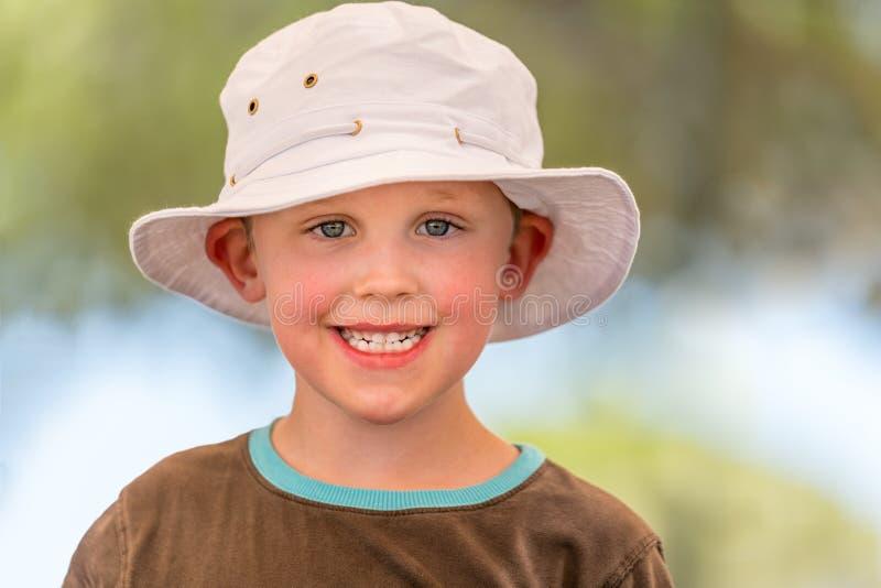Υπαίθριο θερινό πορτρέτο του χαριτωμένου χαμογελώντας αγοριού στο άσπρο καπέλο στοκ φωτογραφία