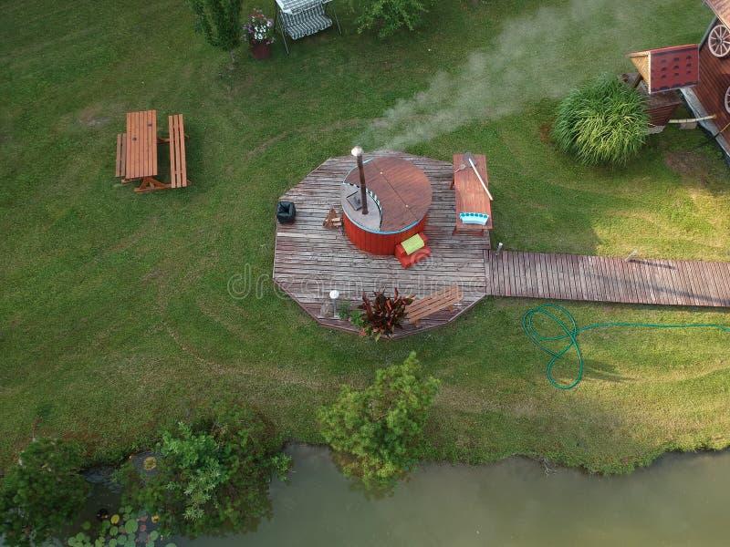 Υπαίθριο ξύλινο λουτρό βαρελιών στο θερινό αγροτικό σπίτι, εναέριο στοκ φωτογραφία με δικαίωμα ελεύθερης χρήσης