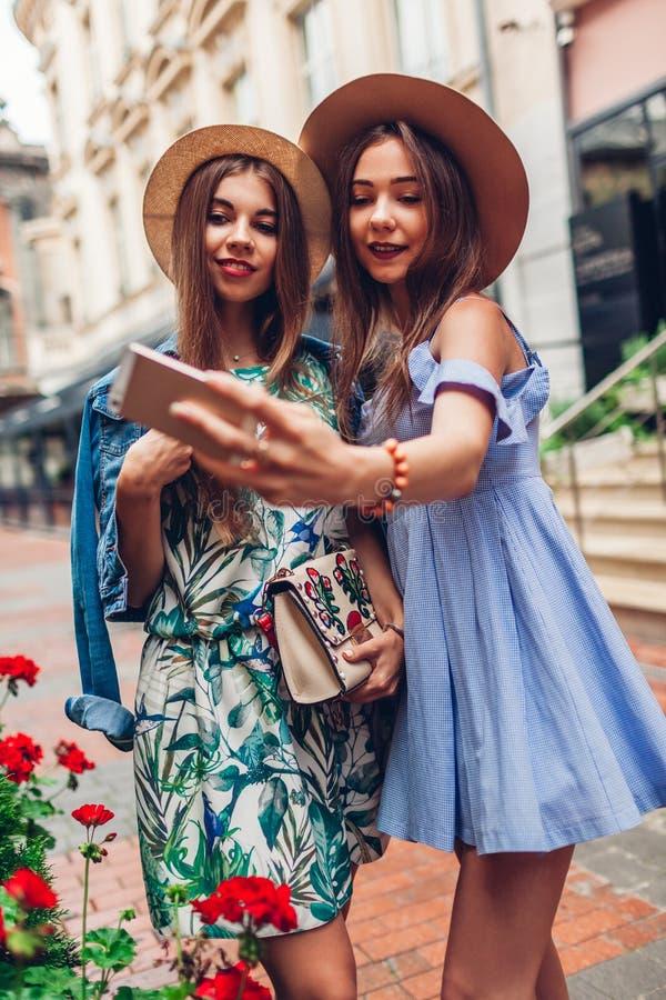 Υπαίθριο πορτρέτο δύο νέων όμορφων γυναικών που παίρνουν selfie χρησιμοποιώντας το τηλέφωνο Κορίτσια που έχουν τη διασκέδαση στην στοκ εικόνες
