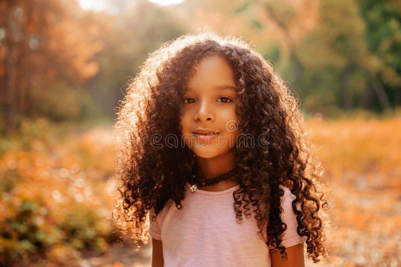 Υπαίθριο πορτρέτο ενός χαριτωμένου μικρού κοριτσιού ευτυχίας afro αμερικανικού με το σγουρό hairl στοκ εικόνα