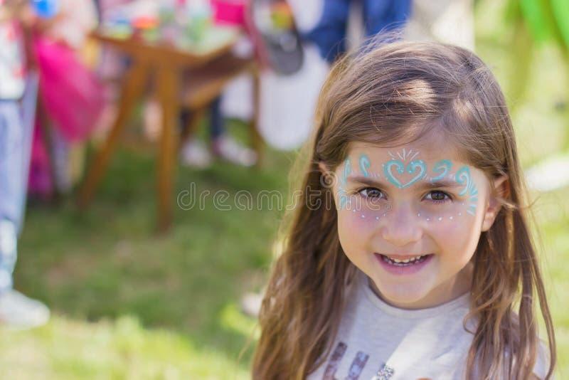 Υπαίθριο πορτρέτο ενός όμορφου μικρού κοριτσιού με το χρωματισμένο πρόσωπο στοκ φωτογραφίες
