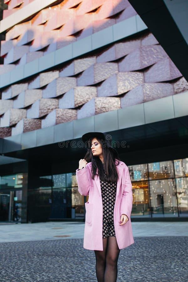 Υπαίθριο πορτρέτο μιας νέας όμορφης μοντέρνης γυναίκας που περπατά στην οδό Πρότυπο φορώντας μοντέρνο ρόδινο παλτό, μαύρο στοκ φωτογραφίες