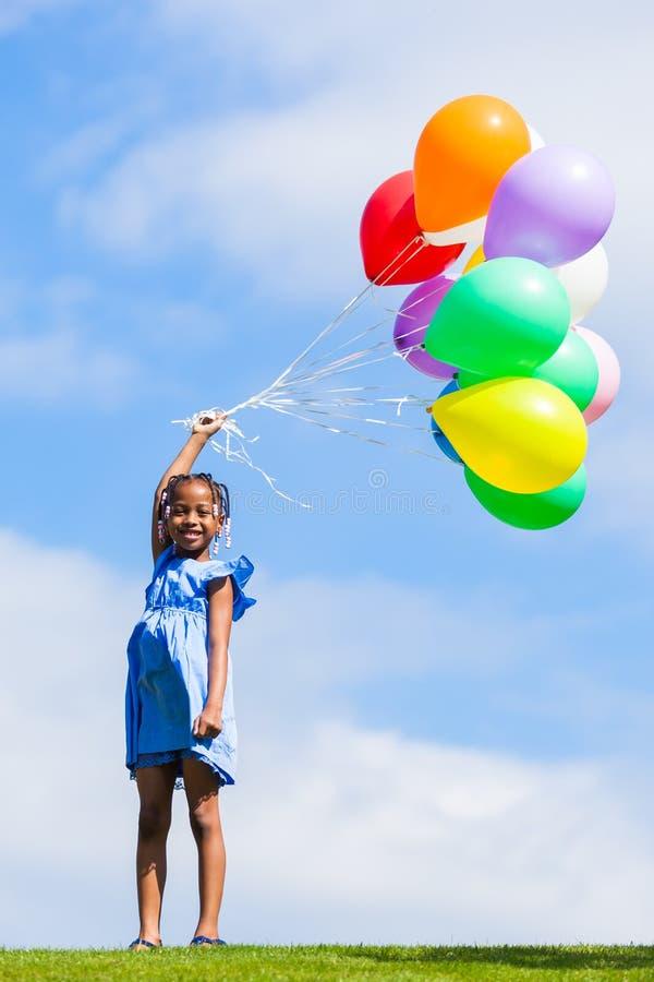 Υπαίθριο πορτρέτο μιας χαριτωμένης νεολαίας λίγο μαύρο κορίτσι που παίζει με στοκ εικόνα με δικαίωμα ελεύθερης χρήσης