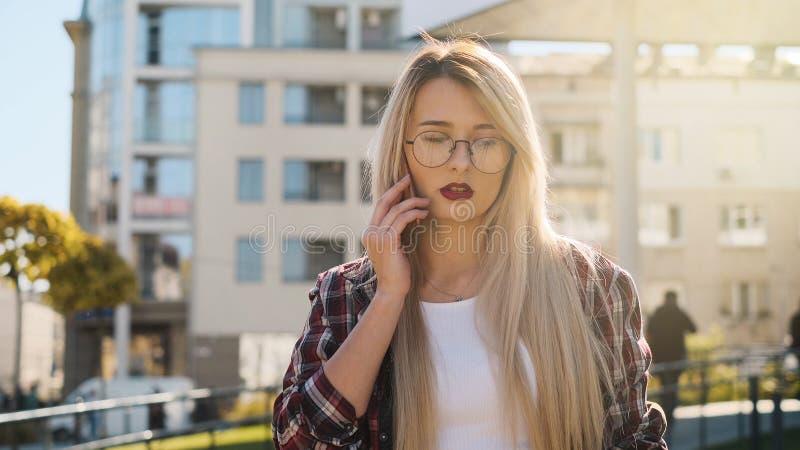Υπαίθριο πορτρέτο μια ξανθή νέα γυναίκα που μιλά από το smartphone της στοκ φωτογραφία