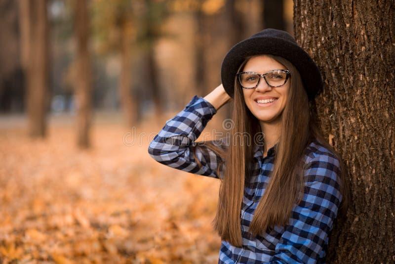 Υπαίθριο πορτρέτο μόδας της νέας γυναίκας με το καπέλο και τα γυαλιά ηλίου το φθινόπωρο, αναδρομικοί τόνοι χρώματος ύφους στοκ φωτογραφία