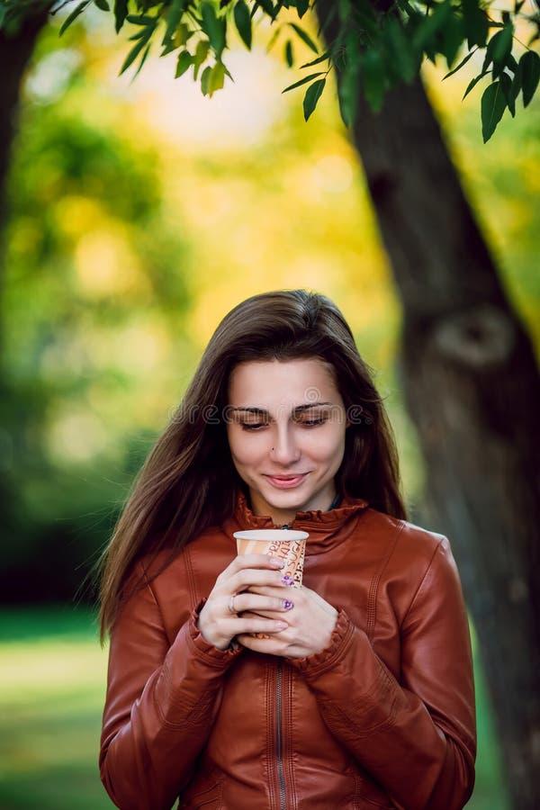 Υπαίθριο πορτρέτο μόδας της πανέμορφης χαμογελώντας γυναίκας στο καφετί σακάκι δέρματος με το φλυτζάνι του coffe Μοντέρνο κορίτσι στοκ φωτογραφίες με δικαίωμα ελεύθερης χρήσης