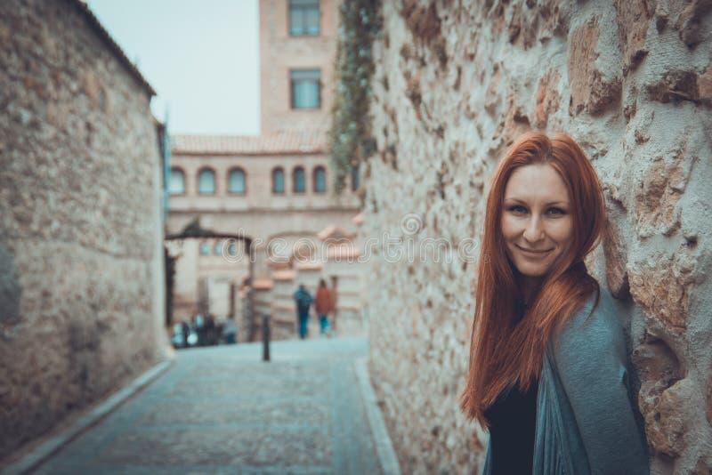 Υπαίθριο πορτρέτο της ελκυστικής νέας γυναίκας με την κόκκινη τρίχα που στέκεται στο κάστρο - τουριστικό αξιοθέατο στοκ εικόνες
