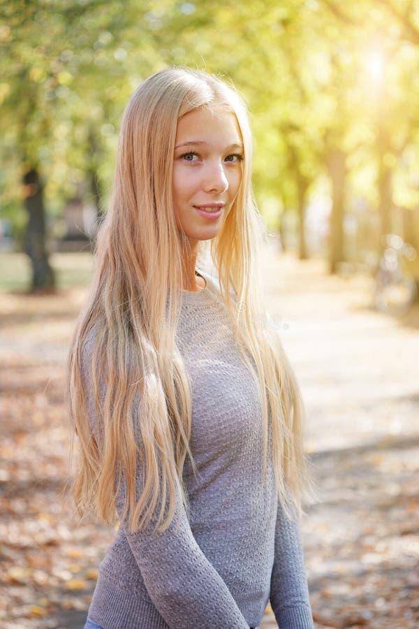 Υπαίθριο πορτρέτο της ξανθής νέας γυναίκας που απολαμβάνει την ηλιόλουστη ημέρα στοκ εικόνες