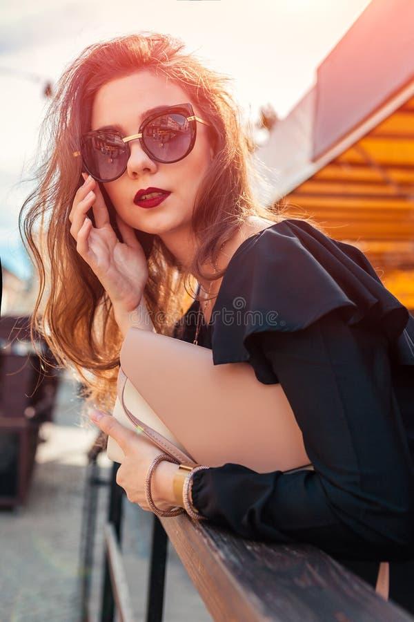 Υπαίθριο πορτρέτο της όμορφης μοντέρνης γυναίκας στα γυαλιά με το makeup Πρότυπα φορώντας θερινά εξάρτηση και εξαρτήματα μόδας στοκ εικόνες