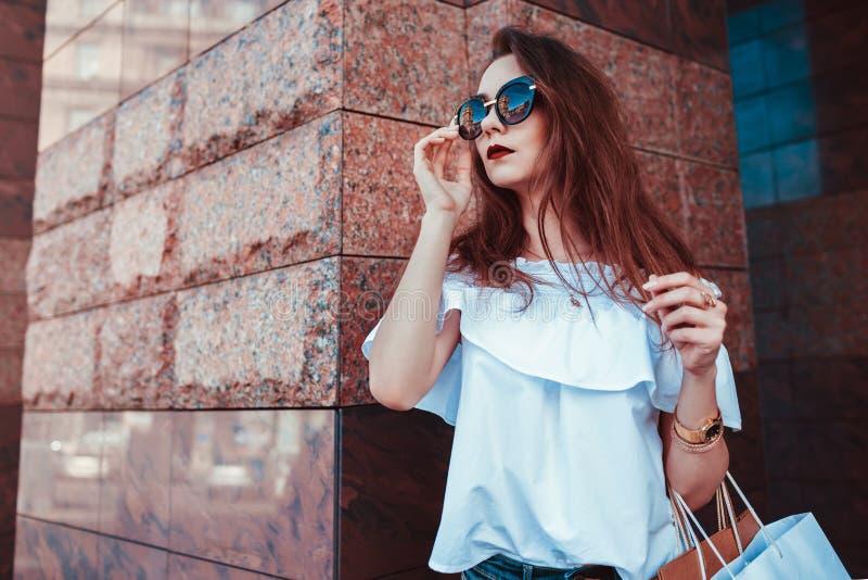 Υπαίθριο πορτρέτο της όμορφης μοντέρνης γυναίκας στα γυαλιά στην οδό Πρότυπο μόδας που φορά το θερινούς ιματισμό και τα εξαρτήματ στοκ φωτογραφία με δικαίωμα ελεύθερης χρήσης