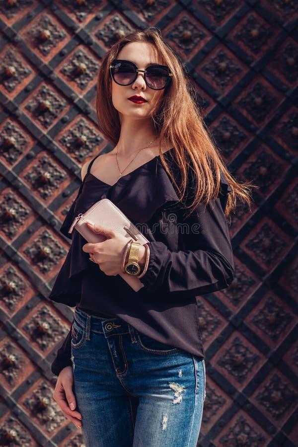 Υπαίθριο πορτρέτο της όμορφης μοντέρνης γυναίκας στα γυαλιά στην οδό Πρότυπο μόδας που φορά το θερινούς ιματισμό και τα εξαρτήματ στοκ εικόνα