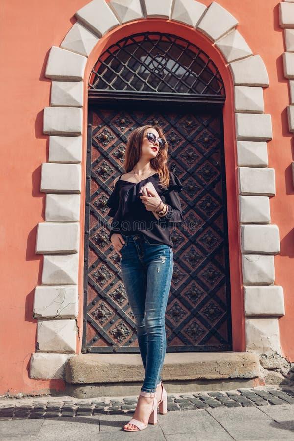 Υπαίθριο πορτρέτο της όμορφης μοντέρνης γυναίκας στα γυαλιά στην οδό Πρότυπο μόδας που φορά το θερινούς ιματισμό και τα εξαρτήματ στοκ εικόνες