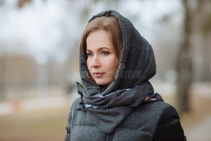 Υπαίθριο πορτρέτο της όμορφης στοχαστικής νέας γυναίκας που φορά το παλτό με την κουκούλα Τονισμένη επίδραση στοκ εικόνα με δικαίωμα ελεύθερης χρήσης
