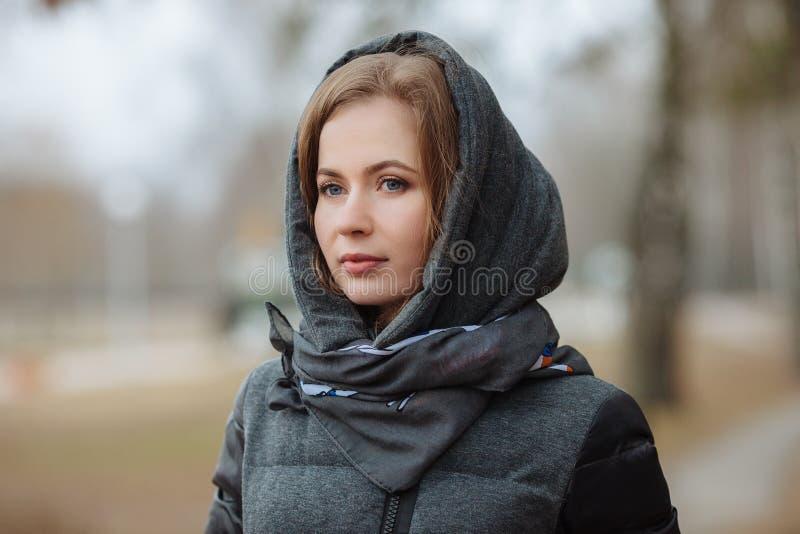 Υπαίθριο πορτρέτο της όμορφης στοχαστικής νέας γυναίκας που φορά το παλτό με την κουκούλα Τονισμένη επίδραση στοκ εικόνες