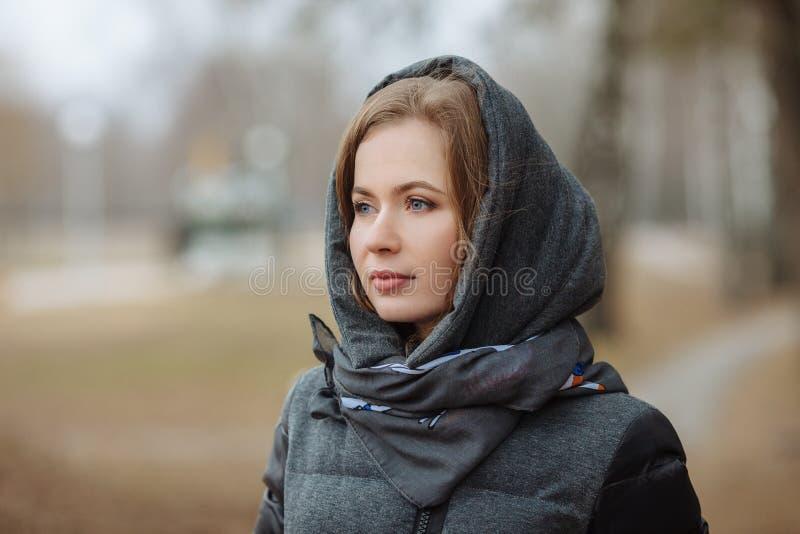 Υπαίθριο πορτρέτο της όμορφης στοχαστικής νέας γυναίκας που φορά το παλτό με την κουκούλα Τονισμένη επίδραση στοκ φωτογραφία με δικαίωμα ελεύθερης χρήσης