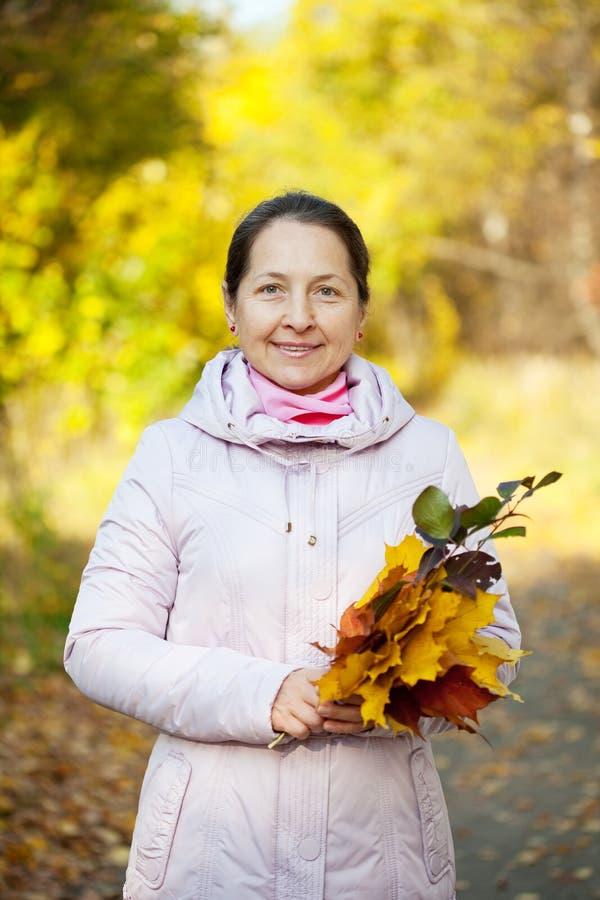 Υπαίθριο πορτρέτο της ώριμης γυναίκας το φθινόπωρο στοκ εικόνες