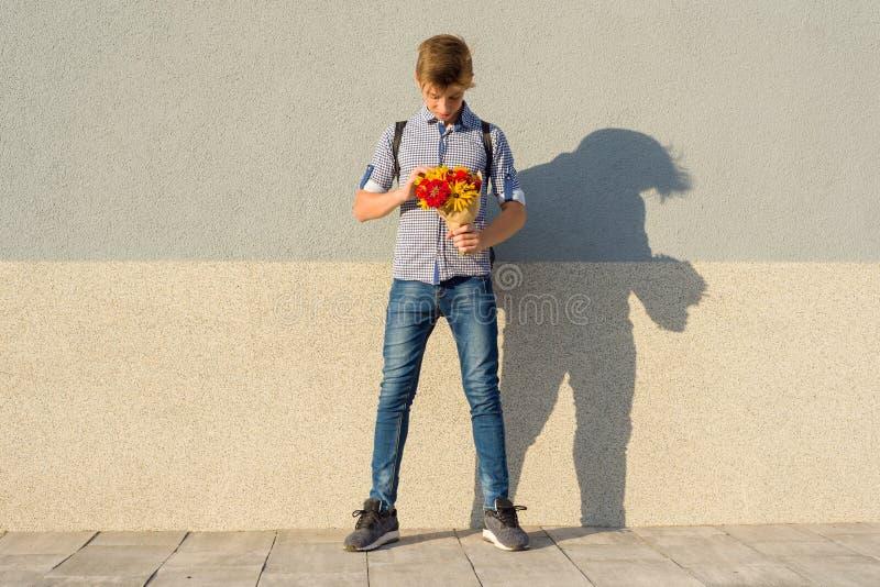 Υπαίθριο πορτρέτο του εφήβου με την ανθοδέσμη των λουλουδιών, γκρίζο υπόβαθρο τοίχων, διάστημα αντιγράφων στοκ φωτογραφία με δικαίωμα ελεύθερης χρήσης