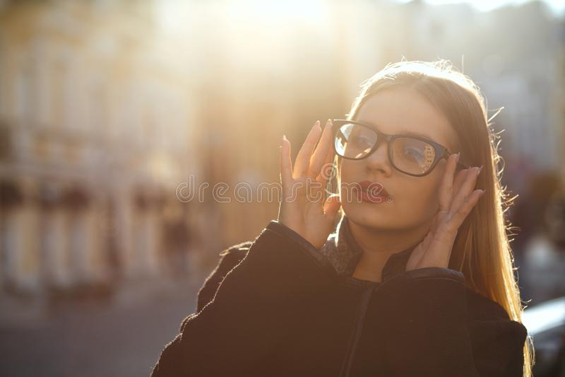 Υπαίθριο πορτρέτο του θαυμάσιου ξανθού κοριτσιού που φορά τα γυαλιά και ομο στοκ εικόνα