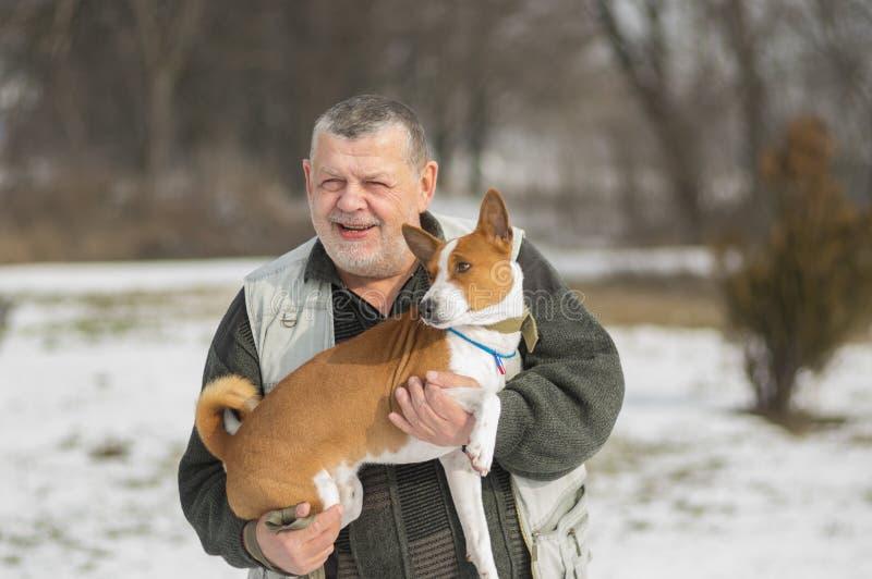 Υπαίθριο πορτρέτο του καυκάσιου ανώτερου ατόμου που παίρνει το καλό σκυλί basenji του στοκ φωτογραφία