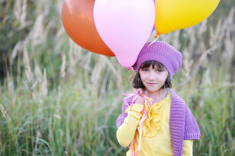 Υπαίθριο πορτρέτο του μικρού κοριτσιού με τα μπαλόνια στοκ φωτογραφία