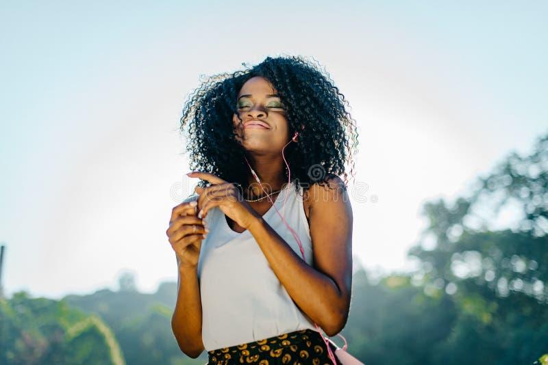 Υπαίθριο πορτρέτο του νέου όμορφου αφρικανικού κοριτσιού με το γοητευτικό χαμόγελο, τη φυσική σύνθεση και πολύ τη σκοτεινή σγουρή στοκ φωτογραφία με δικαίωμα ελεύθερης χρήσης